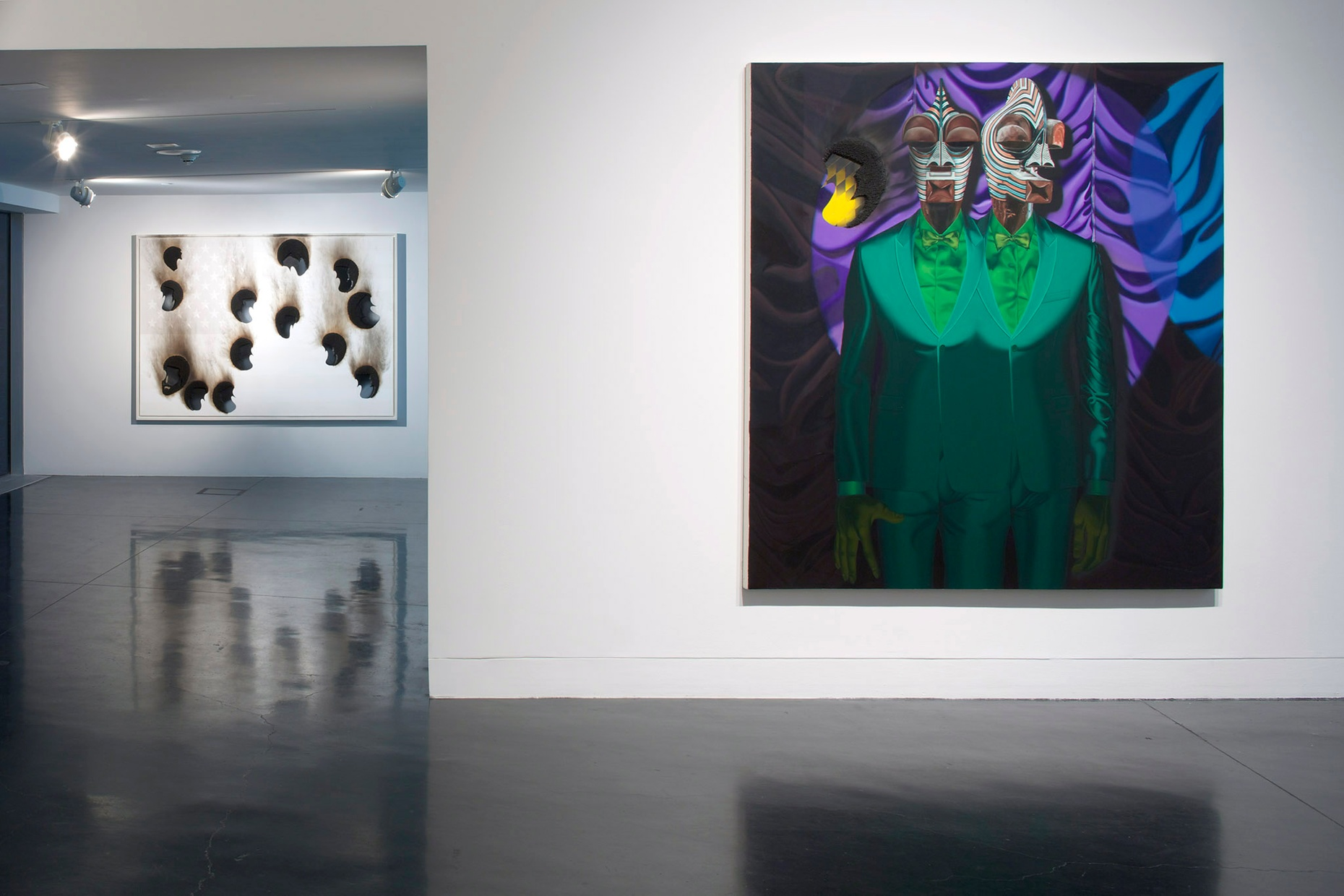 An abstract painting of two Black men in green suits merged together with a black, blue, and purple background hanging on a white wall.