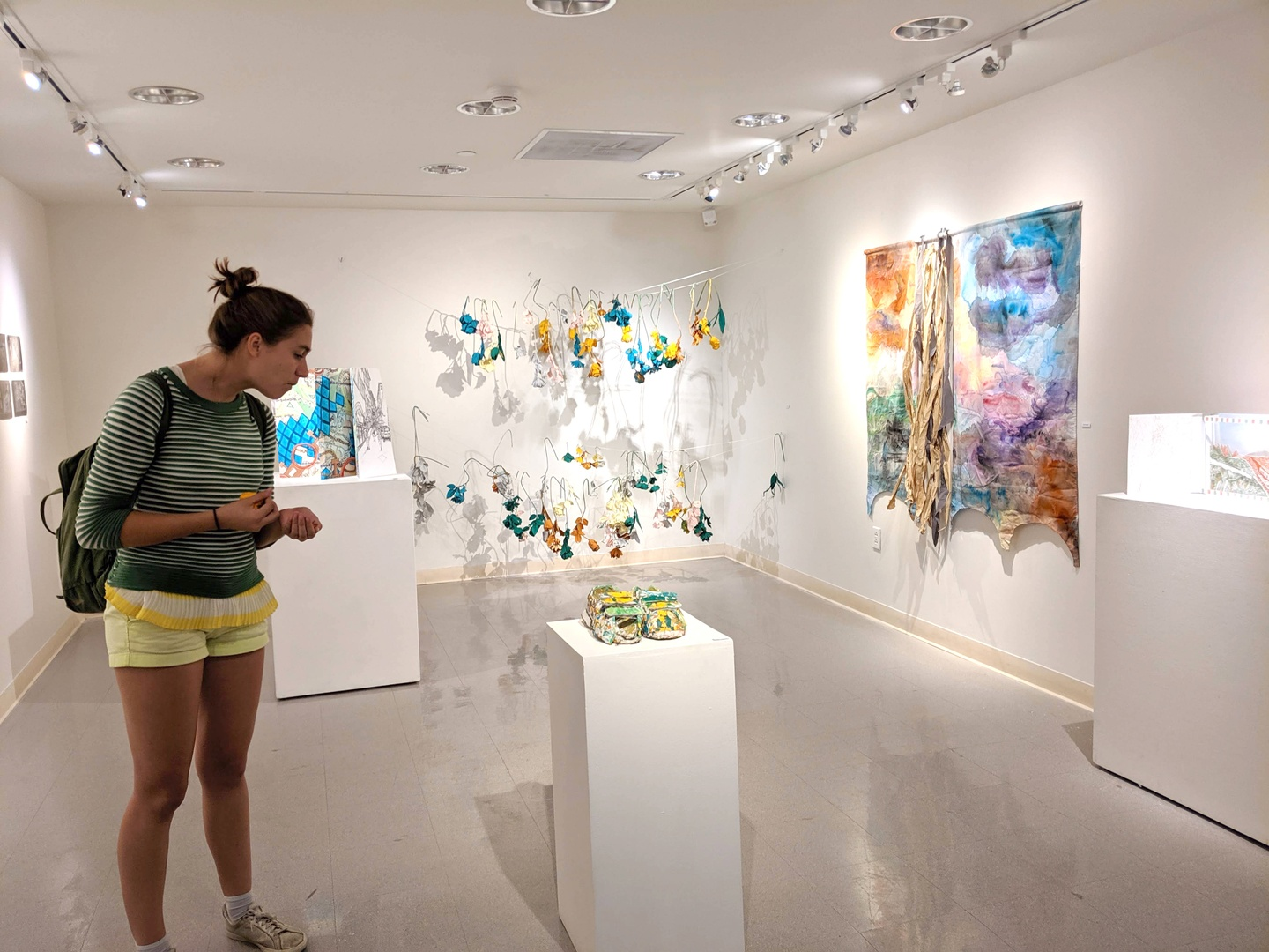 A person looks at an object on a white plinth in a small white-walled gallery space.