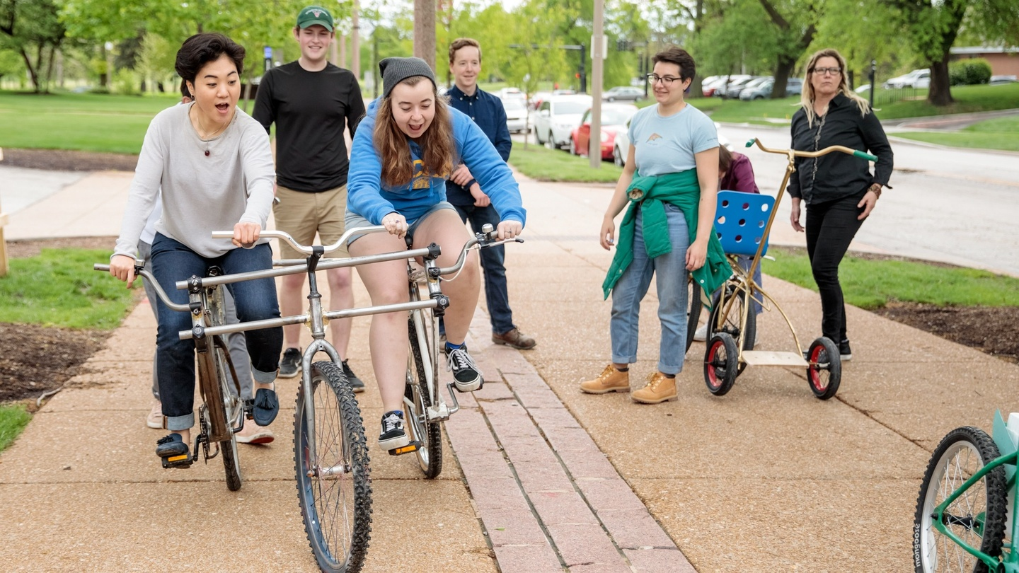 Two people excitedly test-ride a tandem tricycle down a pedestrian path while others look on, holding other unusual wheeled contraptions.