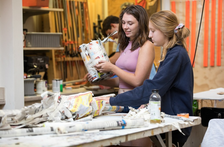 Two people work on a papier mache project at a worktable in a shop space.