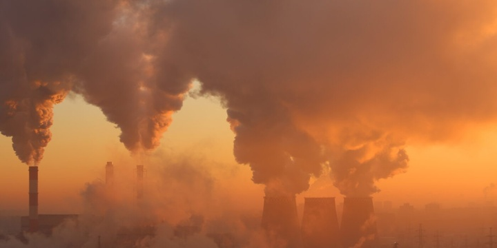 An orange sky with abstracted smoke emerging from unseen several smokestacks.