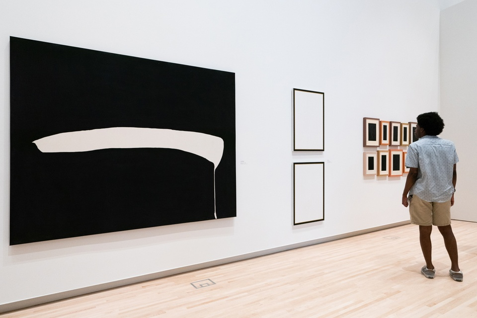 Person looks at a gallery of modern abstract art.