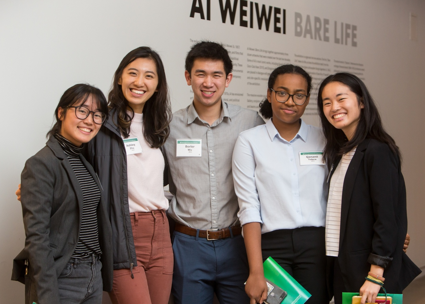 """Five people pose in front of a white wall with vinyl lettering reading """"Ai Weiwei Bare Life."""""""