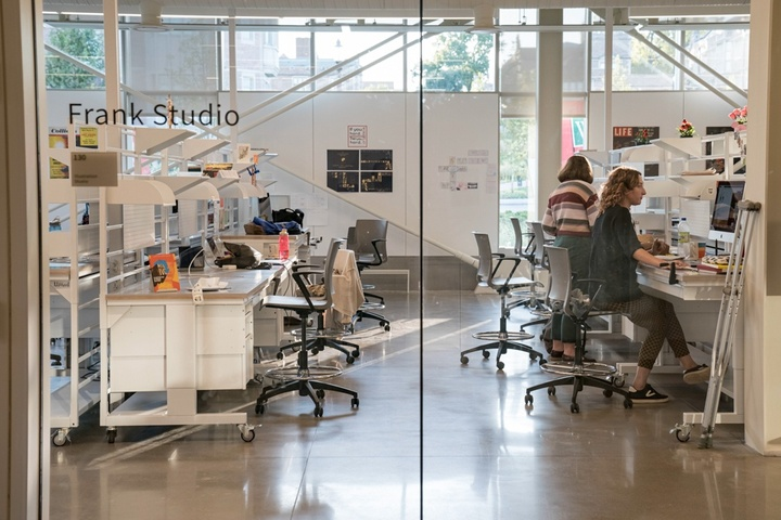 """View into a shared studio space with desks. Vinyl letters on the window say """"Frank Studio."""""""