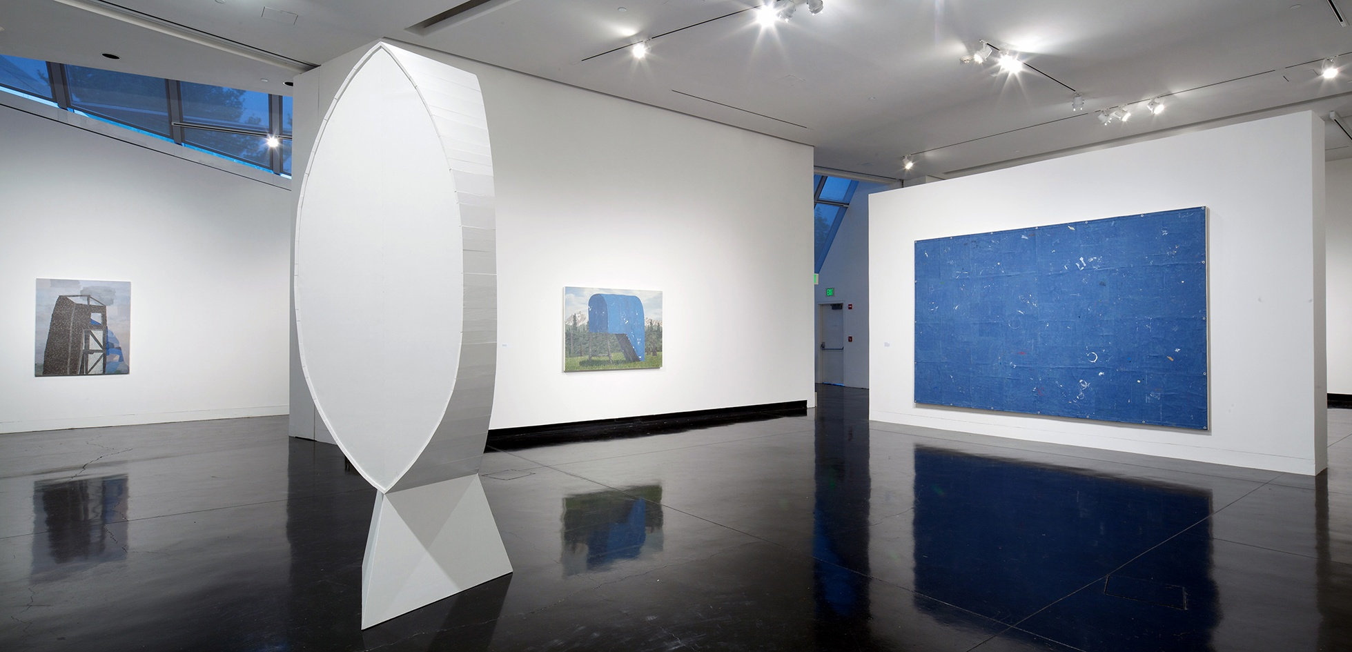 A white, oval sculpture stands in a gallery surrounded by white walls with abstract, landscape paintings on them.