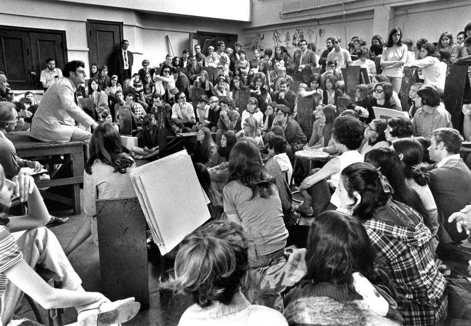 Black and white photo of a packed drawing studio. A person on a dais is speaking, dozens of others are gathered around listening, sitting on drawing horses.