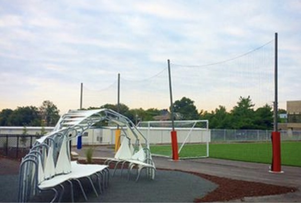 Shade structure made of geometric white forms sits in front of a soccer field.