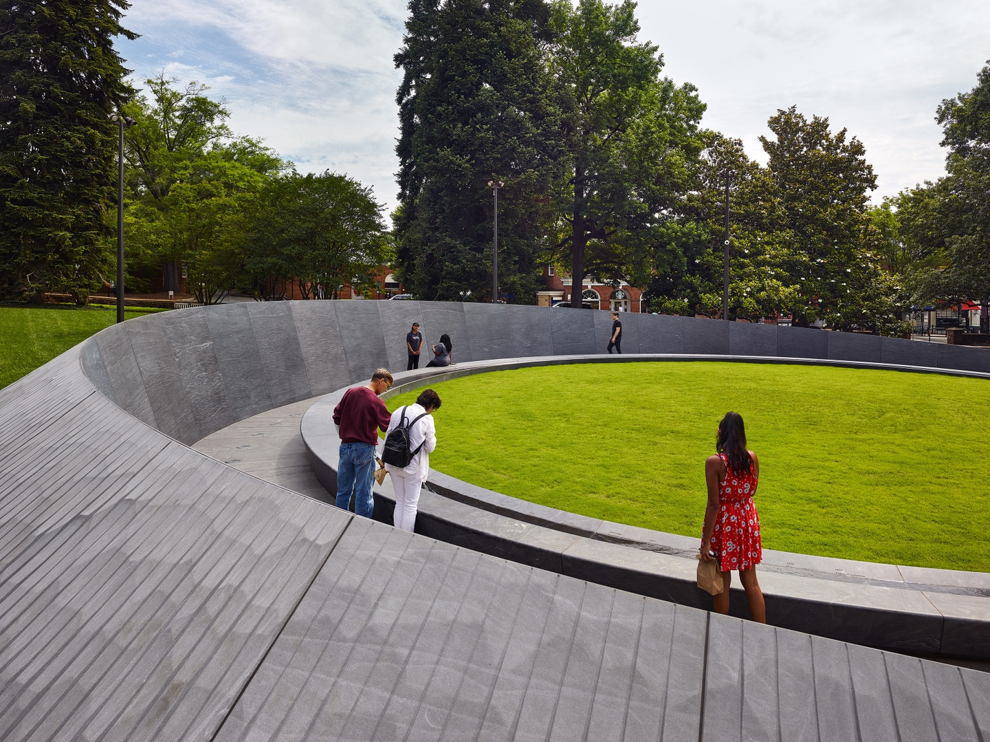 Photo showing a portion of the gray, curved memorial wall, with people walking inside it; the memorial surrounds a ovular patch of grass.
