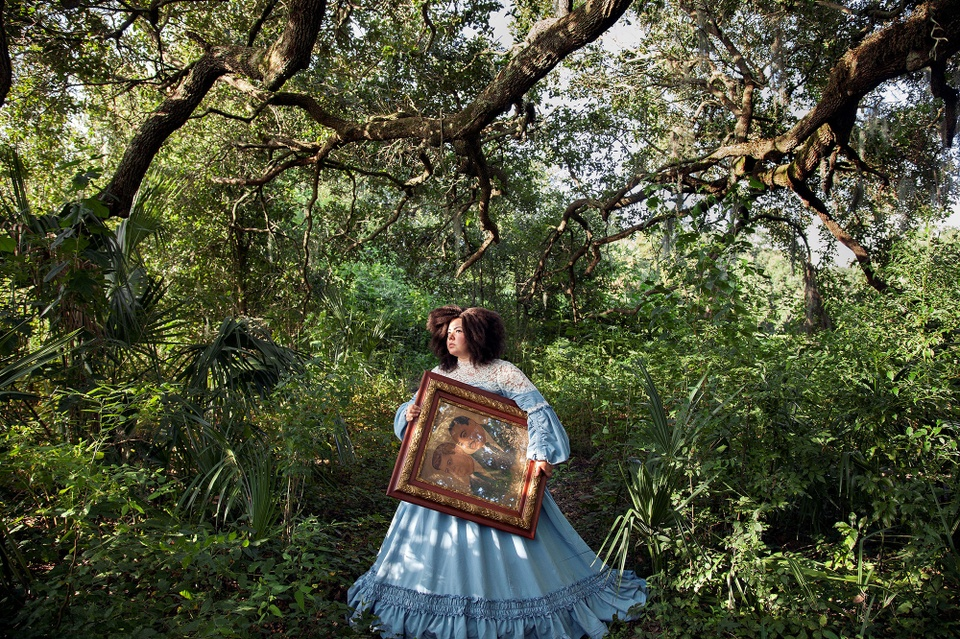 Full-color inkjet print featuring in an elaborate, light-blue, Victorian-era dress, walking through a tree-filled forest carrying a painting.