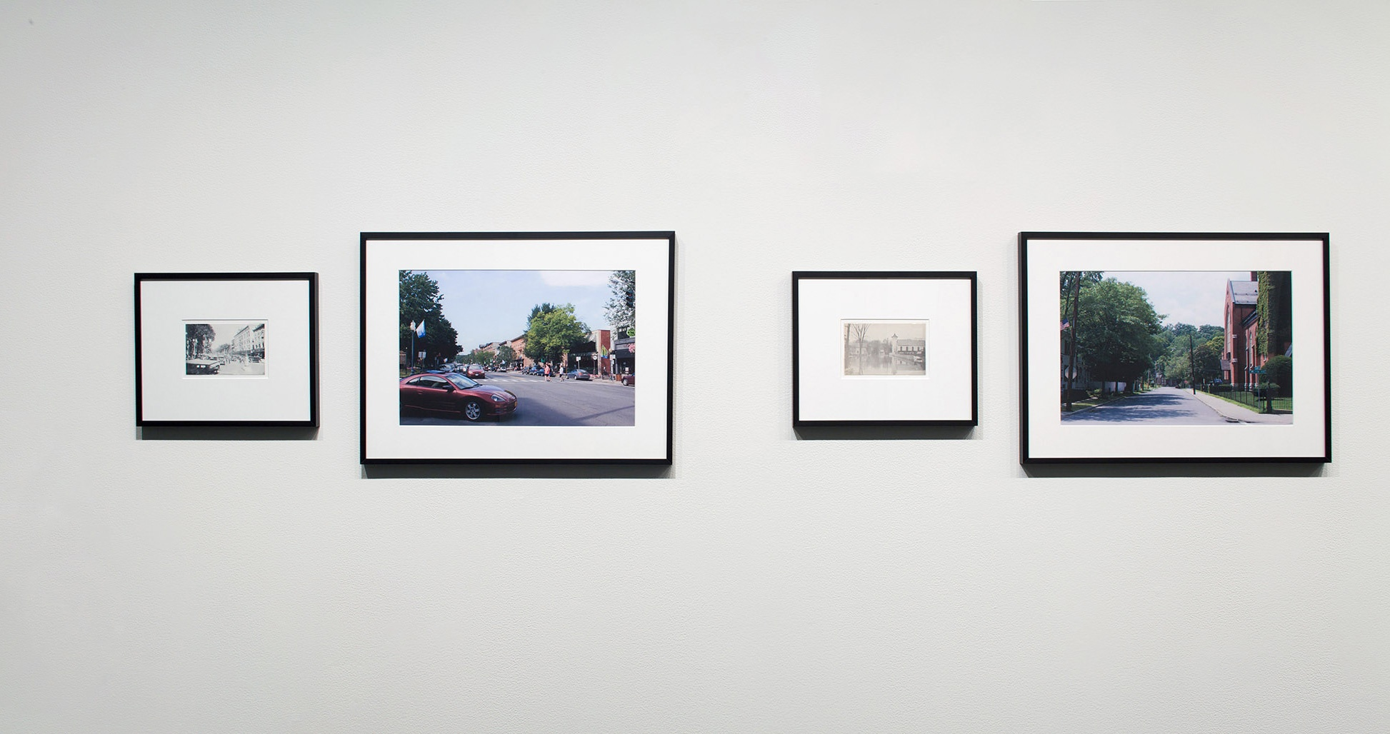 Four framed photographs, two black and white and two colored, of village scenes hang on a white wall.