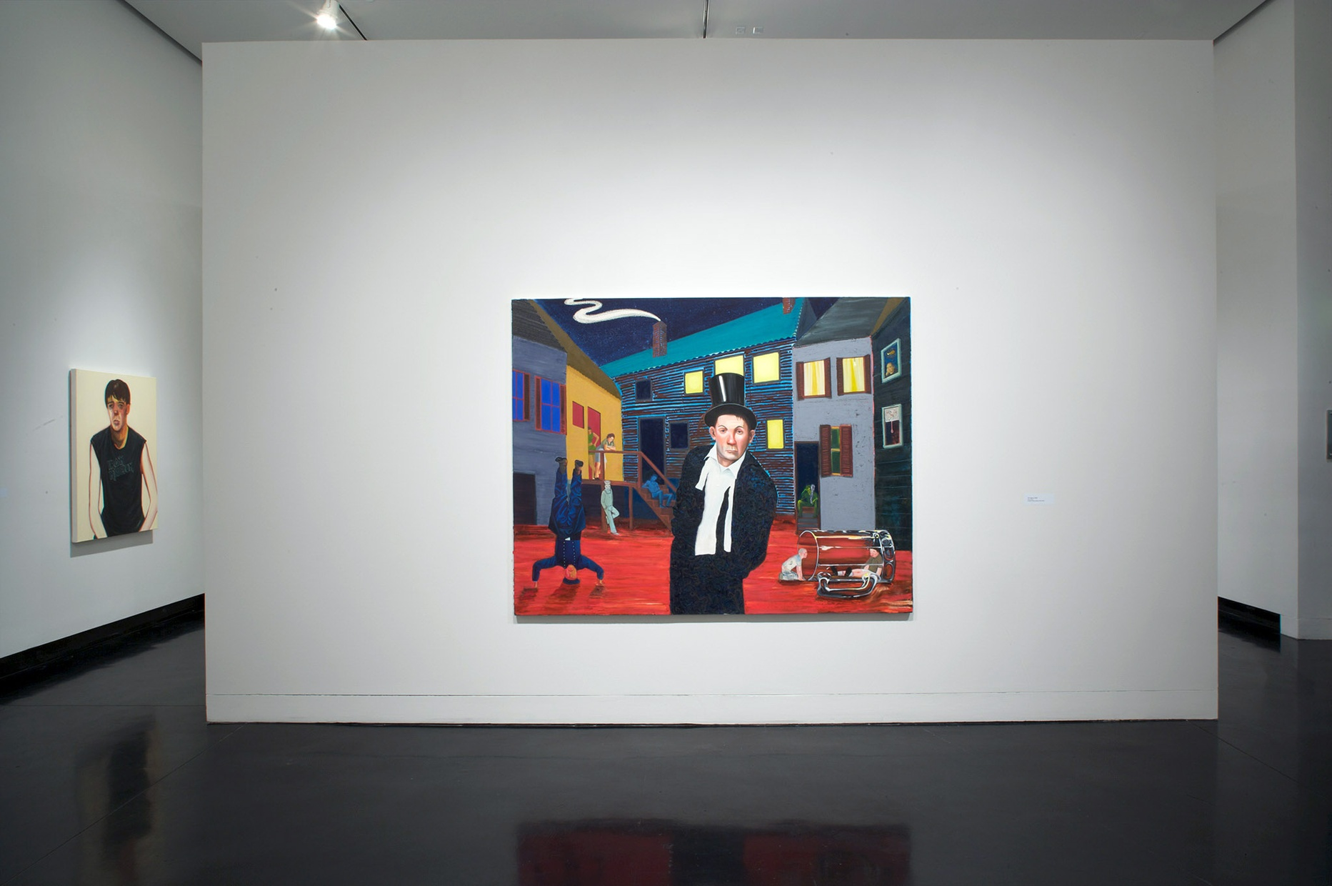 A large, colorful painting of an abstract city scene hangs on a white wall in the center of a gallery.