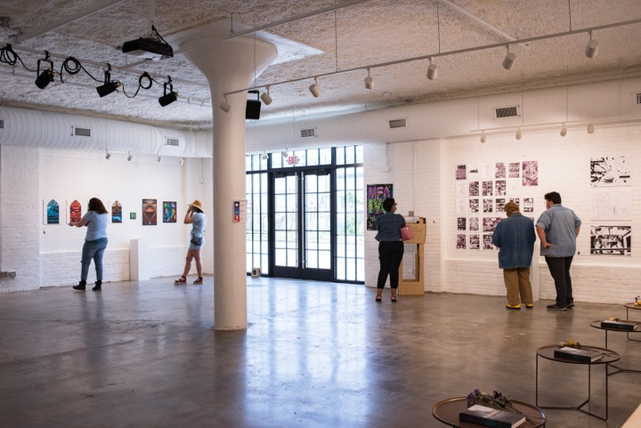 People look at illustrations projects displayed in a modern gallery space with an industrial aesthetic.