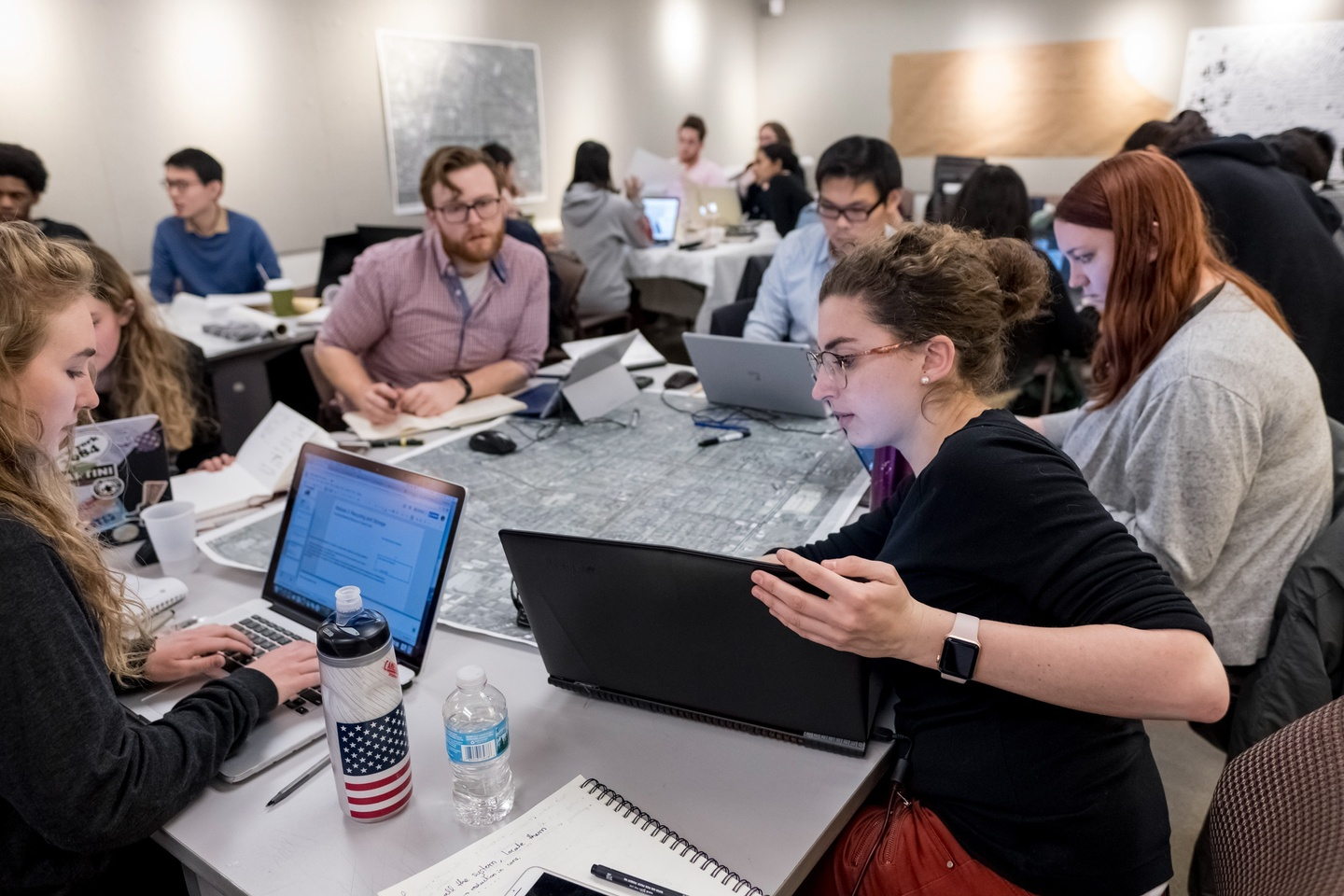 Numerous people gathered at several different tables working; the group in the foreground is gathered around a large map, and several individuals are working on their laptops.