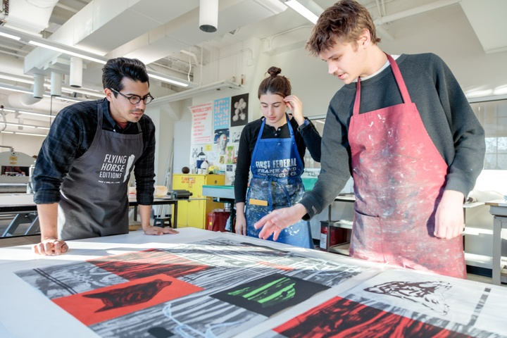 Three students are working in the printmaking studio, gathered around a table with red, white, and black prints.