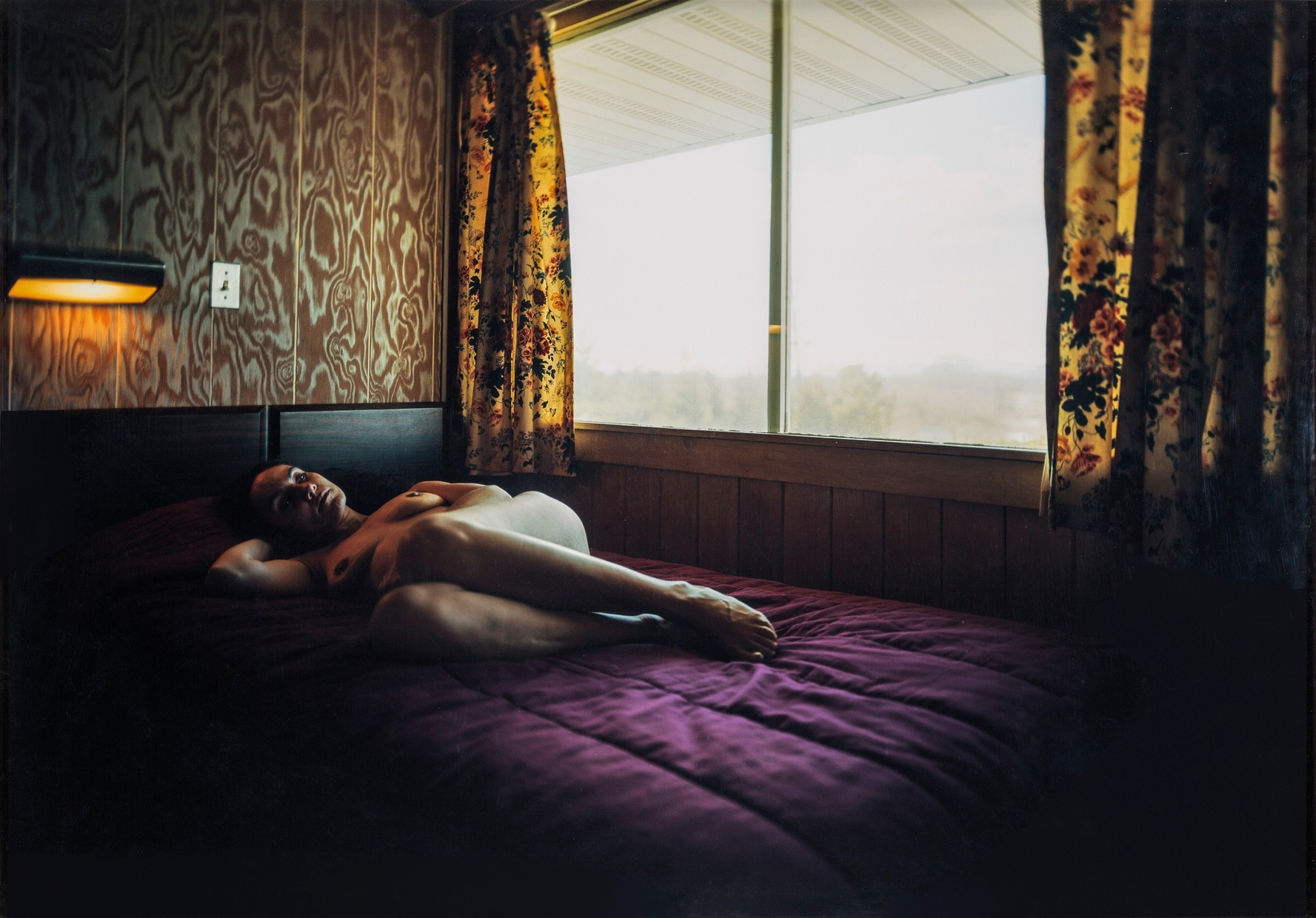 A photograph by Malerie Marder of a naked light-skinned woman laying down on a bed beside a window in a dimly lit room.