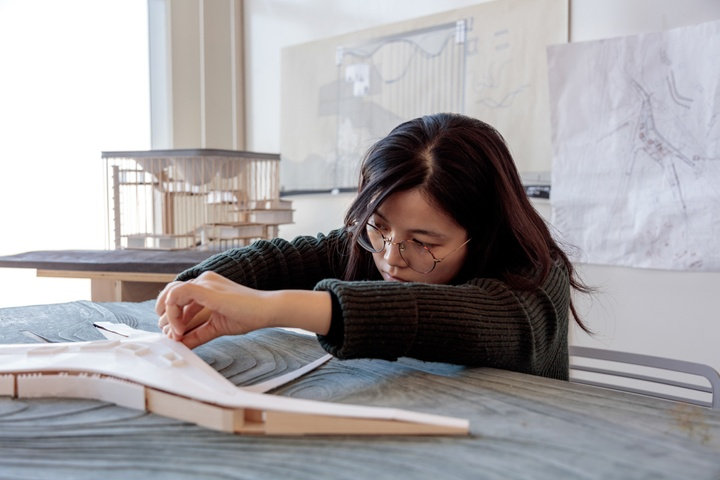 Student working carefully on a ligher-colored architectural model, sitting atop a gray raised topo map. Architectural work is pinned up on a board behind her.