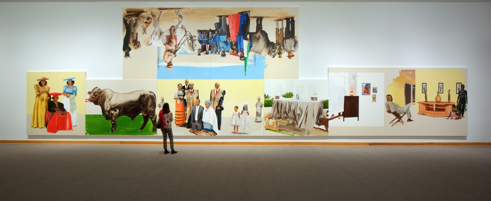 Museum installation of several brightly painted canvases. Five are lined up in a row on the bottom; one hangs above them, hung upside down.