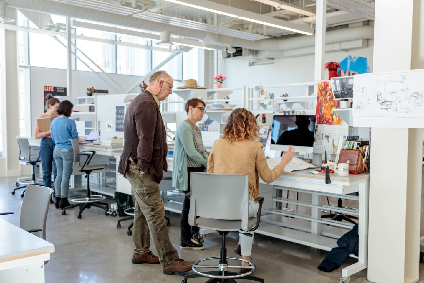 Two faculty gather next to a student at her desk, looking at work; other students are in the background of the light-filled studio space.