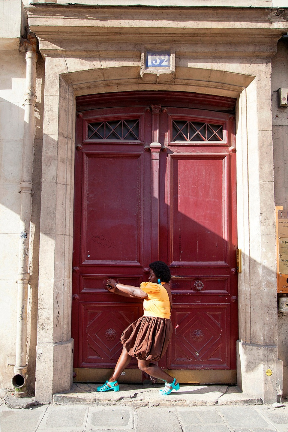 Photograph of an individual in a gold shirt, brown skirt, and teal shoes pulling on one knob to a huge, burgundy double door that is framed by stonework.
