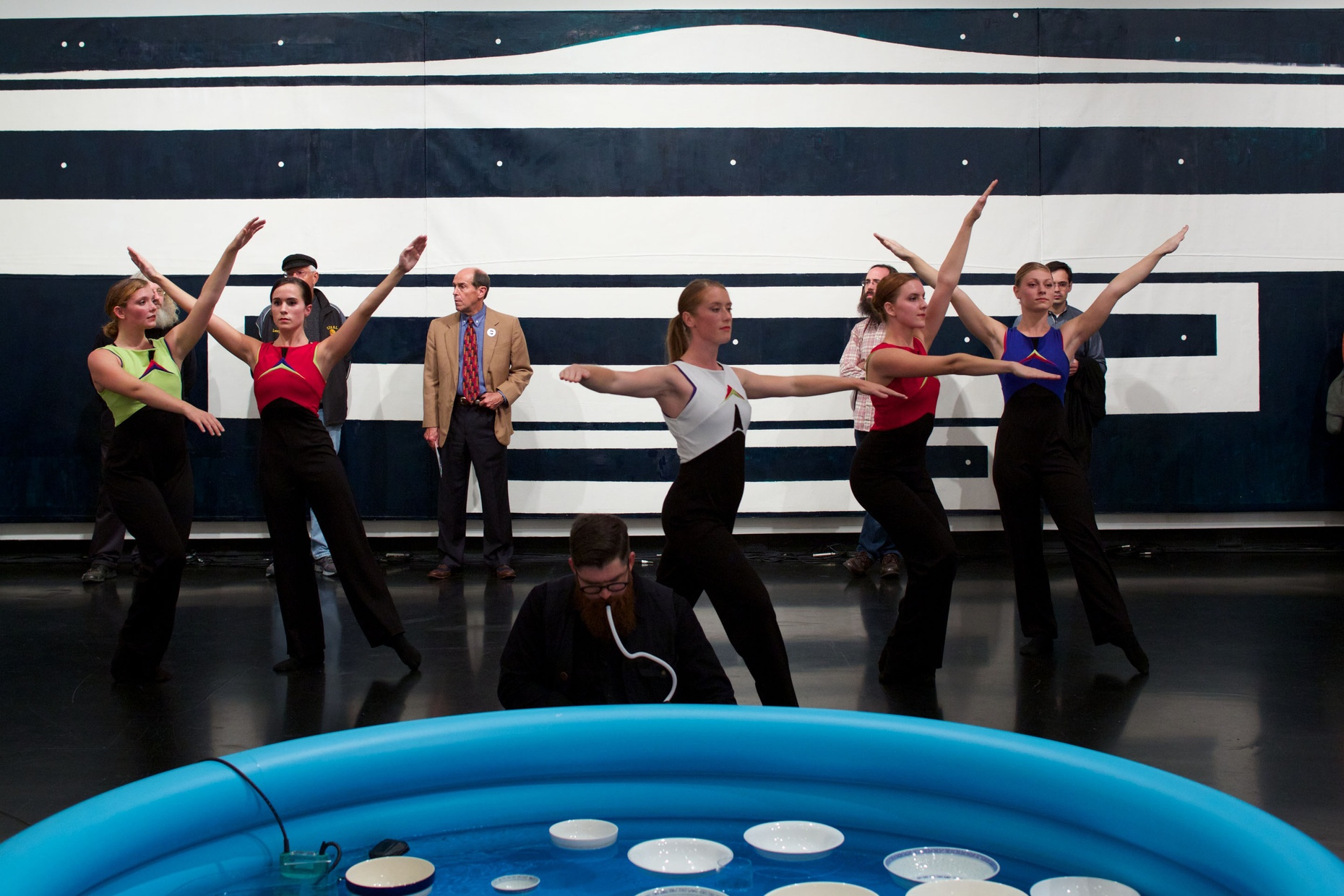 A group of light-skinned, female dancers pose in front of a black and white painted wall with a group of people looking on. In front of the dancers, there is a blue, blow-up pool with white bowls floating in it and a man crouching by it.