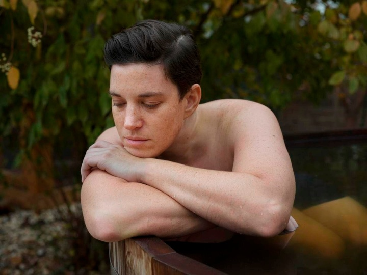 A person sits pensively in an outdoor bathtub