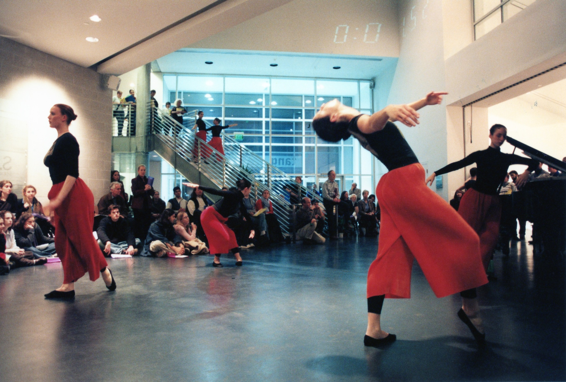 A group of dancers perform in an open space with a crowd of people sitting on the floor around them.
