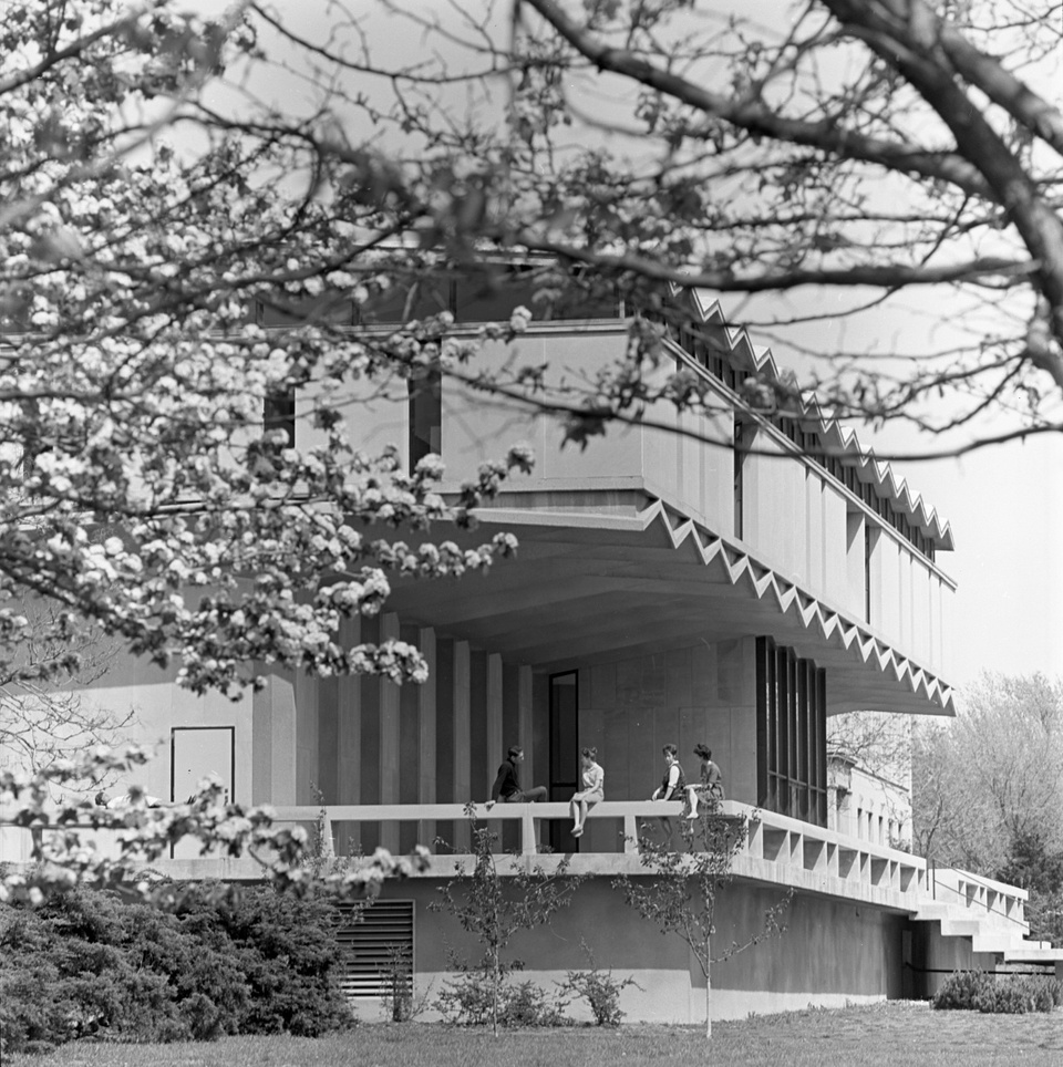 Black and white photo of the corner angle of a midcentury modern building with a large patio. Four people are perched on the patio railing, talking.