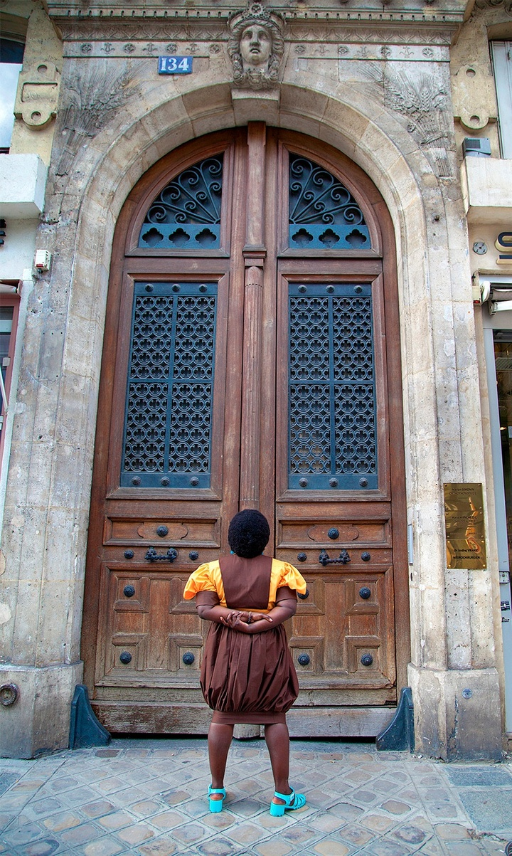 Photo of an individual with their back to the camera, stairing at a massive, curved wooden double door with glass inlay. Stonework frames the door.