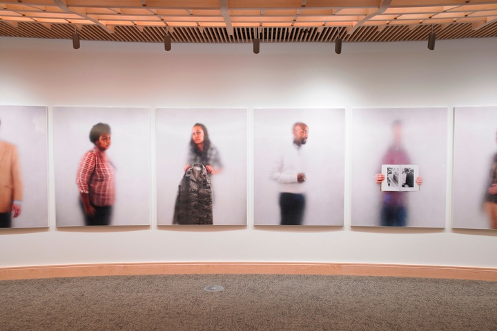 Artwork installation on a rounded wall, featuring a series of individual portraits translated into porcelain enamel panels.
