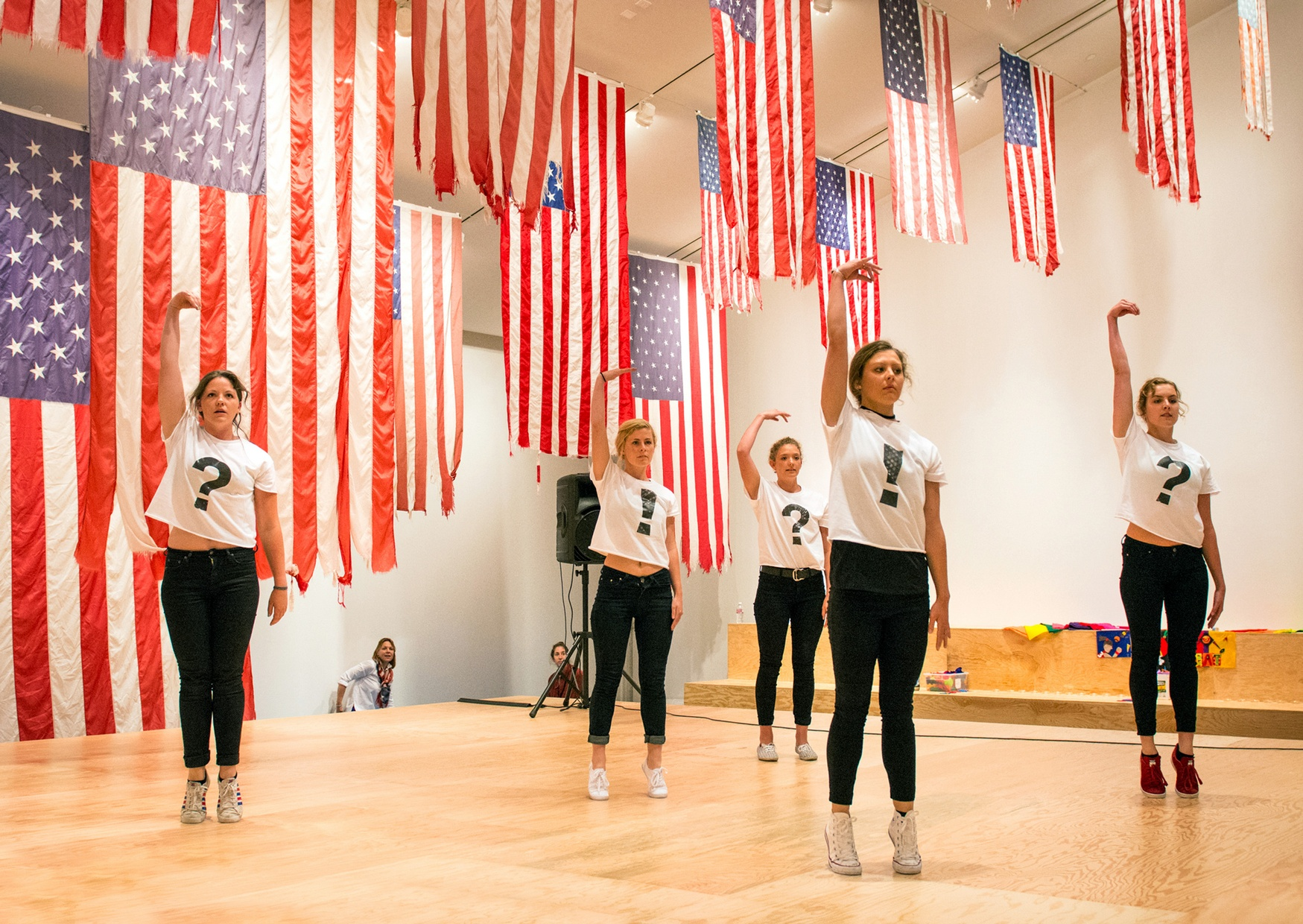 Five light-skinned females pose with one arm raised on a wooden stage surrounded by American flags hung from the ceiling.