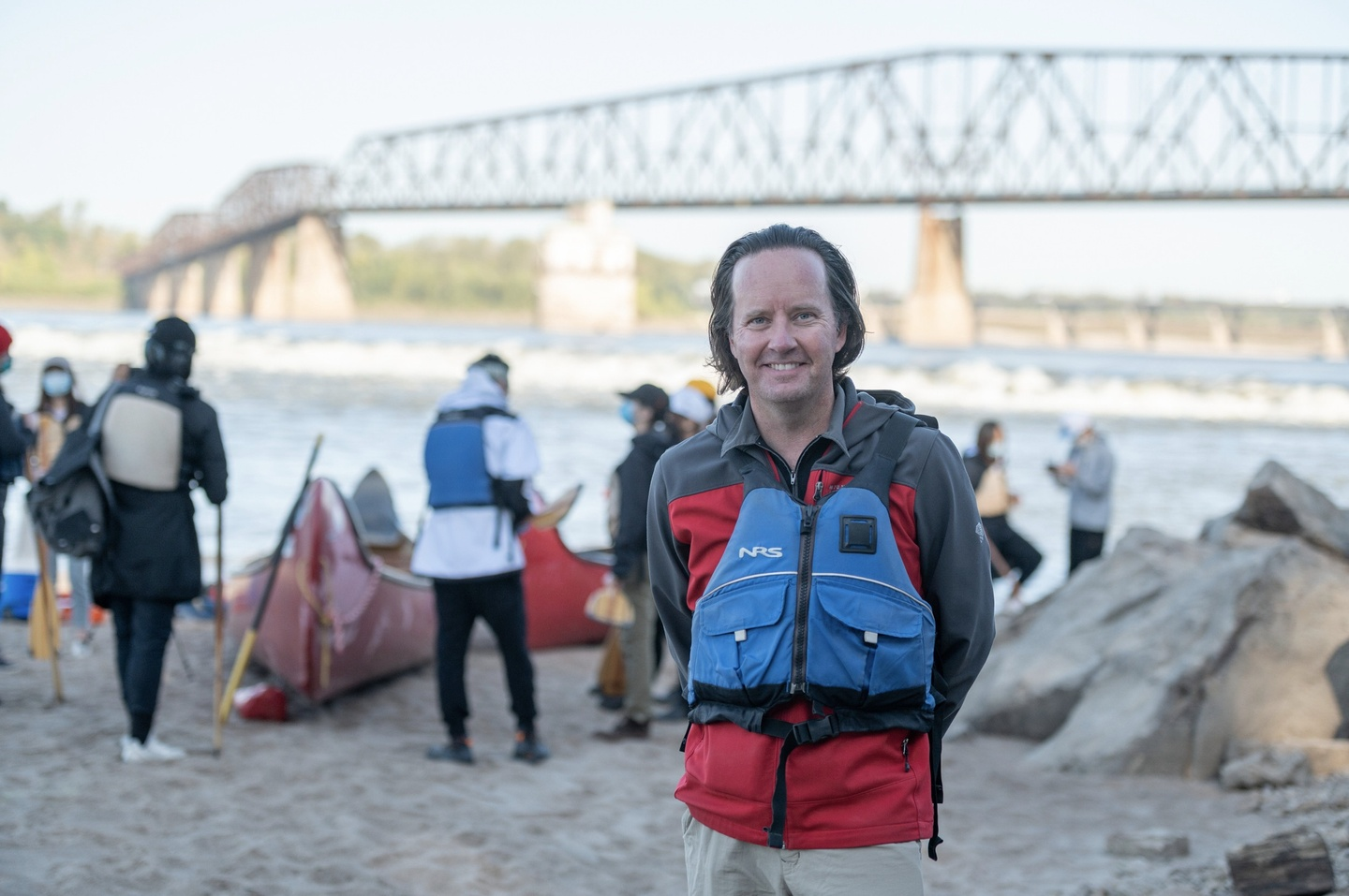 Person with blue life jacket stands in the foreground, in front of the waterfront and bridge. In the background, students prepare to get into canoes.