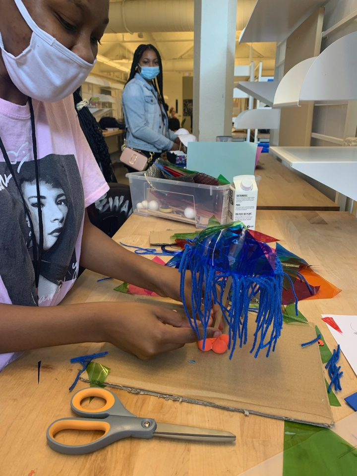 A student works on a model using cardboard and yarn.