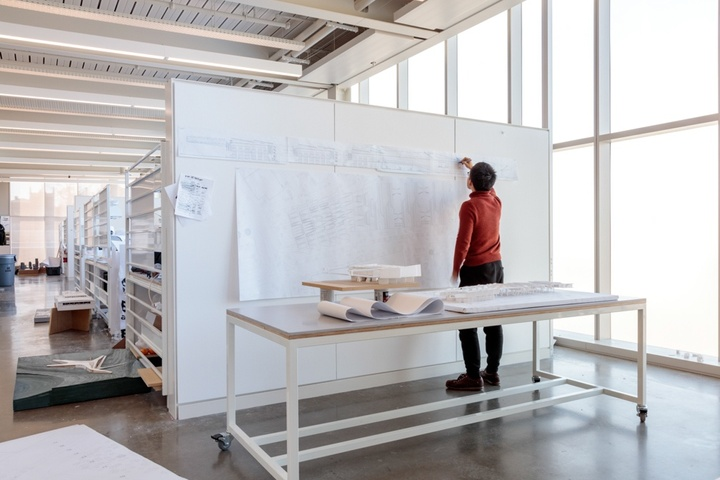 Person stands at a freestanding pin-up wall inspecting a large format printout, behind a table holding a model. Frosted windows take up the wall to the right.