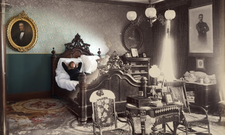 Image of an ornately decorated room that starts in full-color on the left and shifts to black-and-white as you pan across the image. Several framed portraits hang on the walls; an individual is lying down in an ornate bed in the middle of the room, with numerous chairs in front of it and a bookshelf and desk to the right.