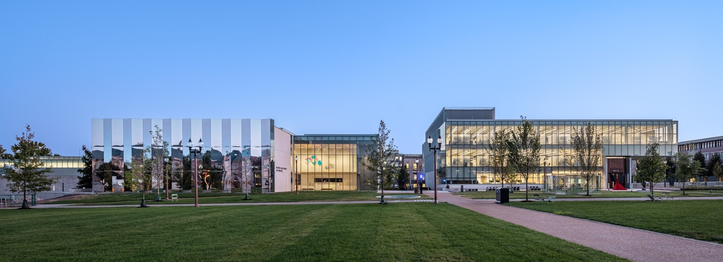 Wide angle shot of two buildings on a college campus. The left one has a pleated exterior mirrored facade and the right is a 3-story glass walled building lit from within.