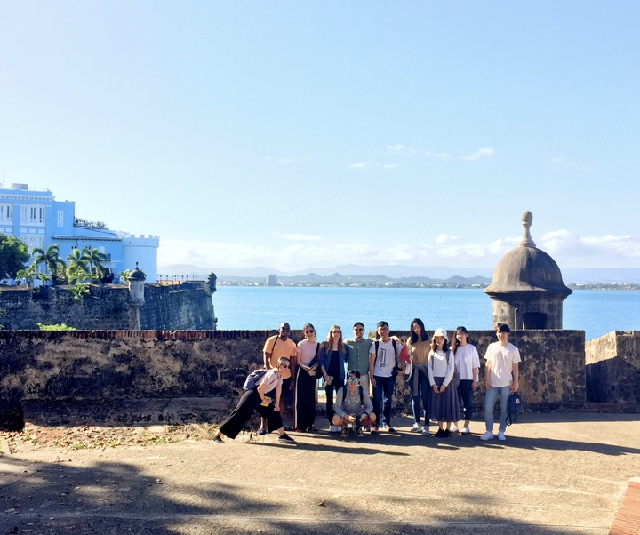 Group of students standing outdoors, in front of an old stone wall in San Juan, Puerto Rico, with the waterfront in the background.