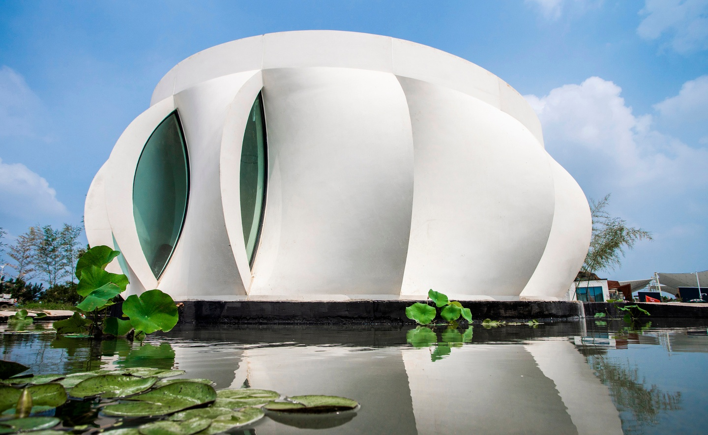 Photo of the exterior facade of a single-story home during the day. The exterior is composed of curved, overlapping panels, arrayed around a central axis like a blossoming flower. Water and lily pads are in the foreground, in front of the home.