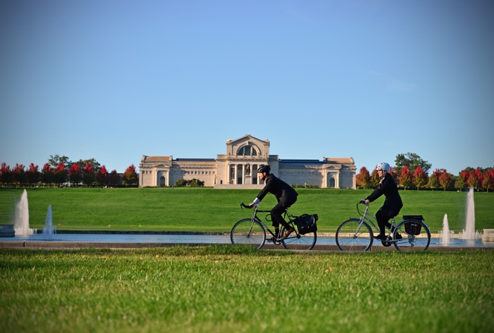 Two people ride bikes along the edge of a pond with fountains. At the top of the hill behind is the Saint Louis Art Museum.