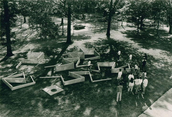 Black and white photo - overhead view of people on a lawn assembling a maze-like structure out of wooden ties.