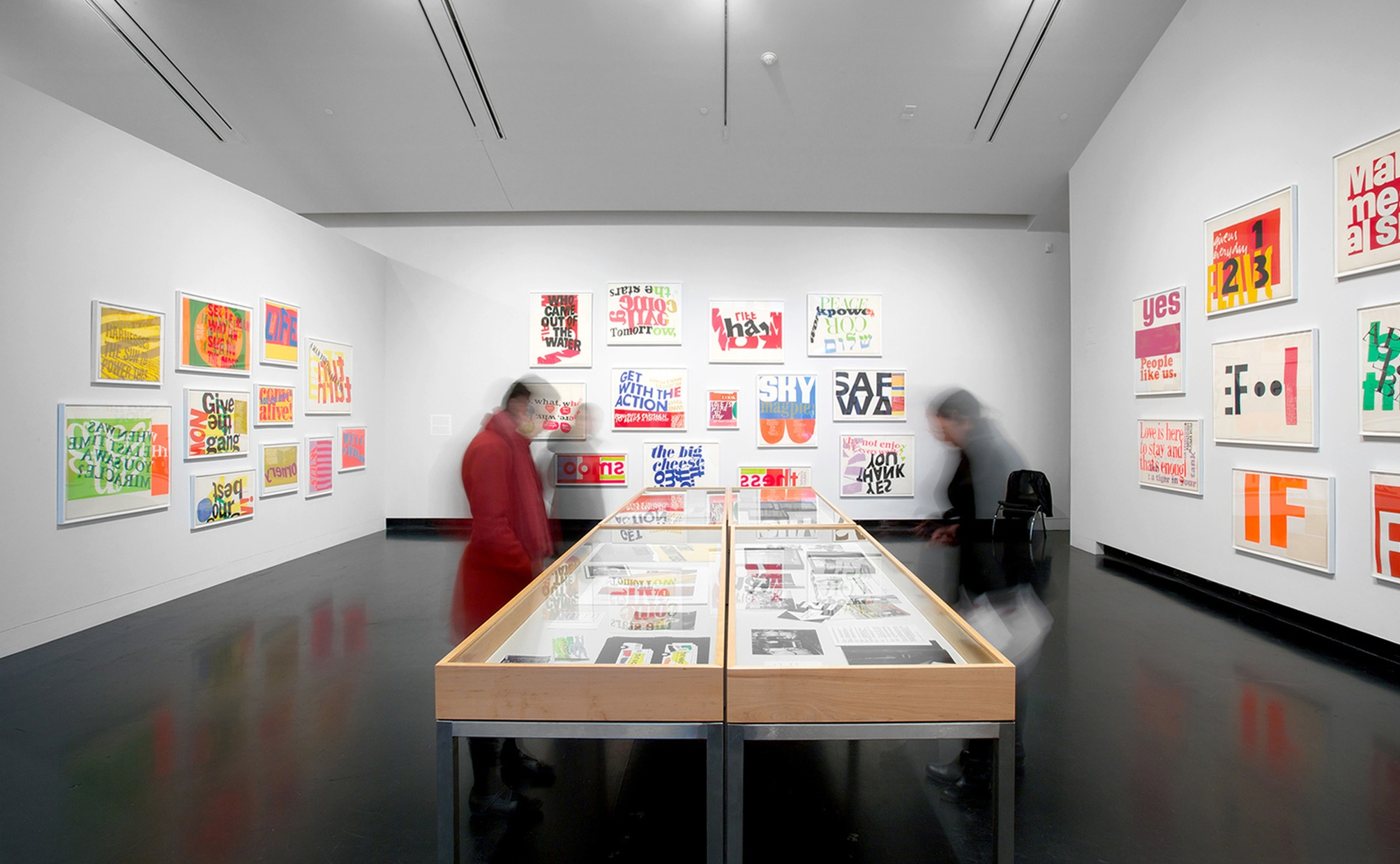 Two wood and glass cases with screenprints inside in the middle of a gallery space with white walls and colorful prints hung on the walls.