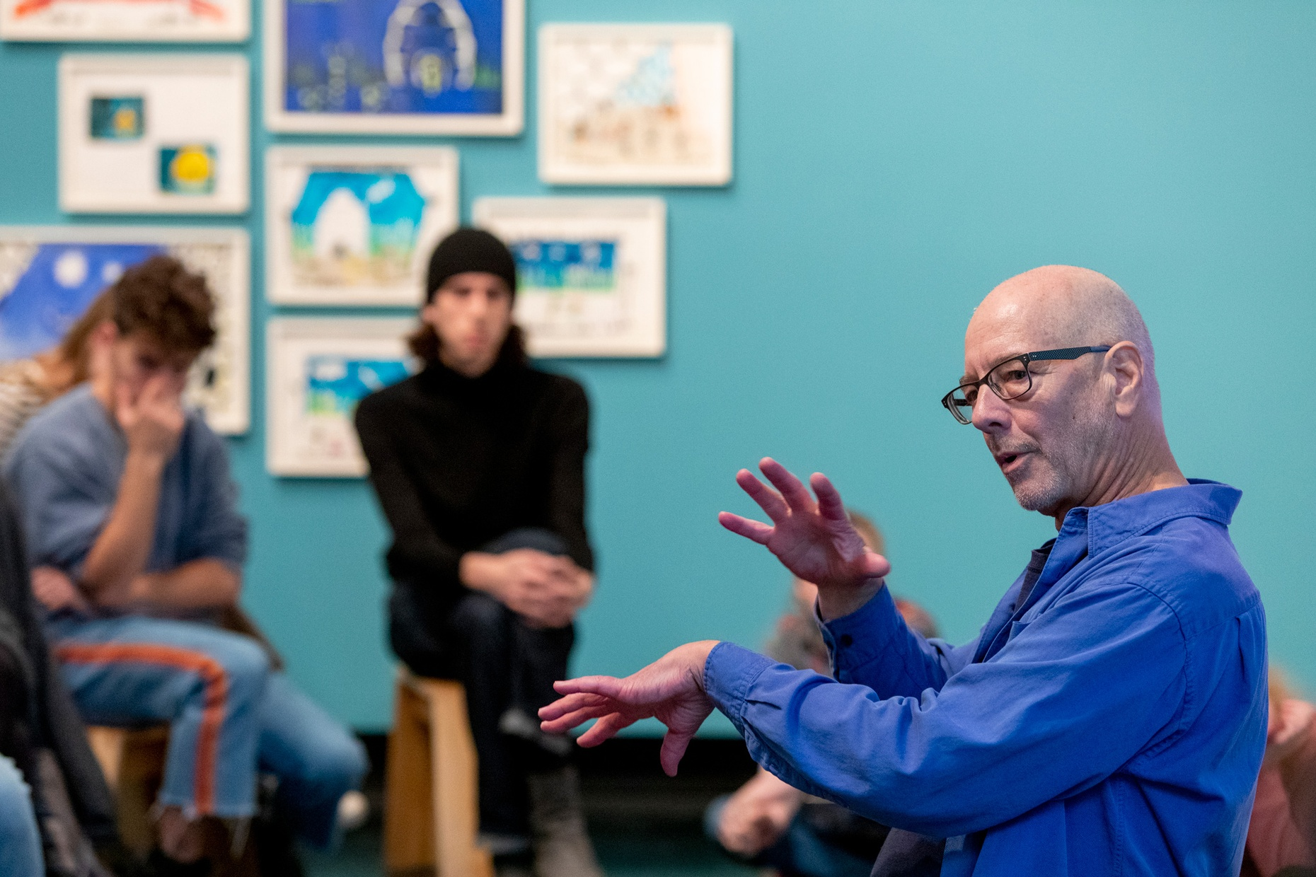 A white, older male talks to a group of people in front of a blue wall.