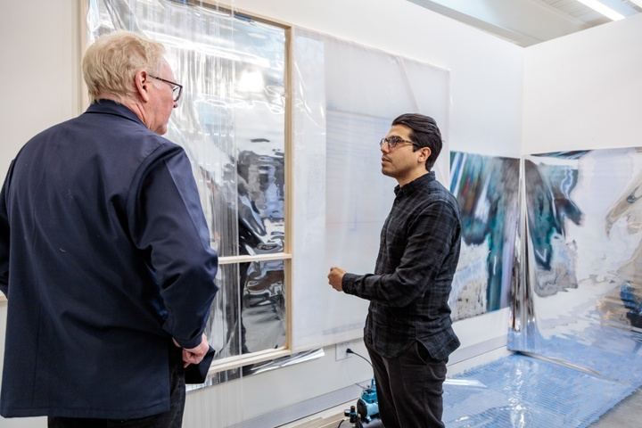 Two people look at a set of artworks hung on the white walls of a private studio space.