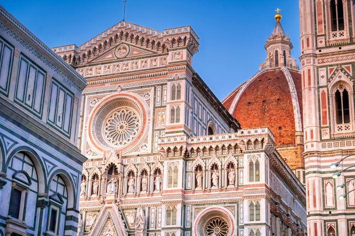 The Santa Maria del Fiore cathedral lit in sunset with a blue sky.