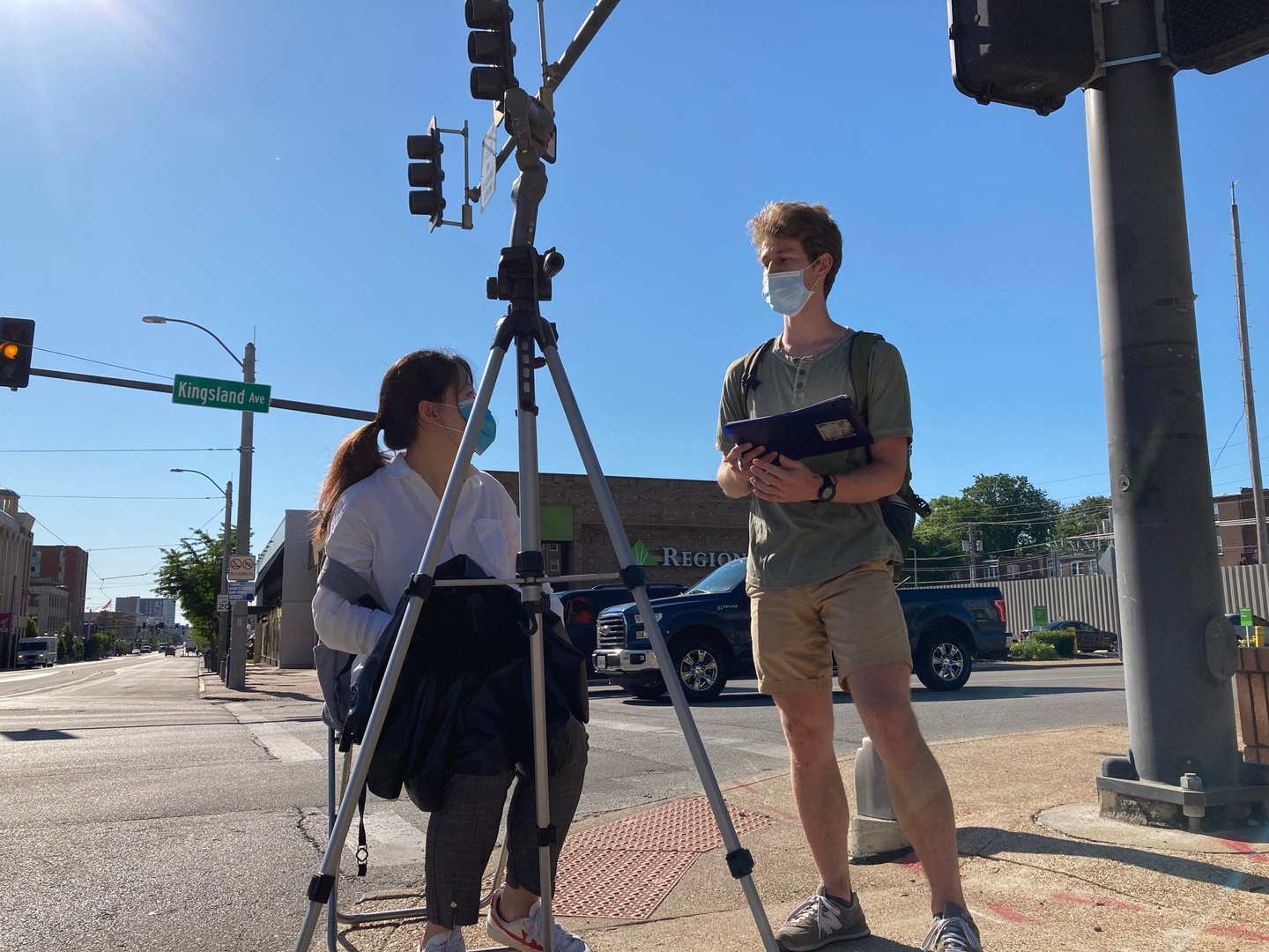 Two students at the intersection of streets, with a street sign for Kingland on a stoplight overhead. One student, seated behind a tripod, is speaking to the other student who is standing. Both are wearing face masks.
