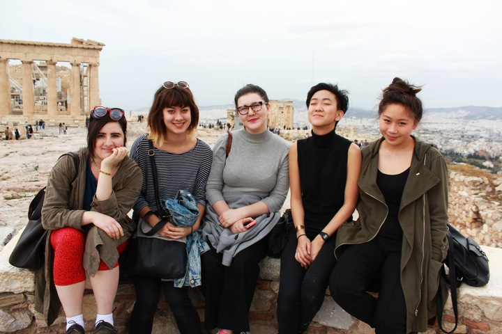 Four people sitting on a low wall in front of the acropolis in Athens, Greece.