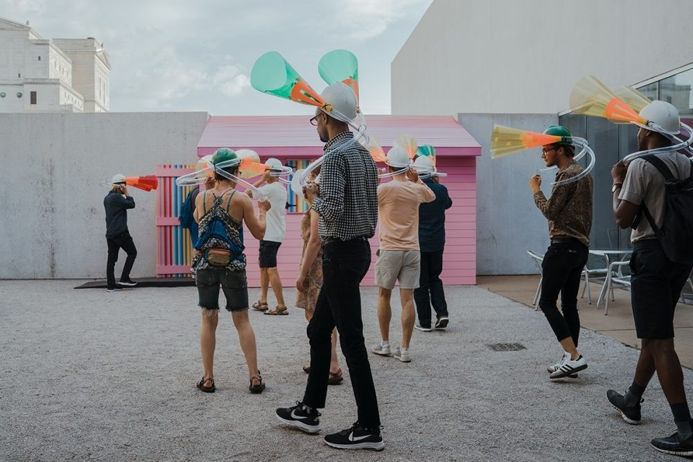 Group of people wearing cylindrical sound pieces as headwear approaching a pink colored house installation at the Contemporary Art Museum