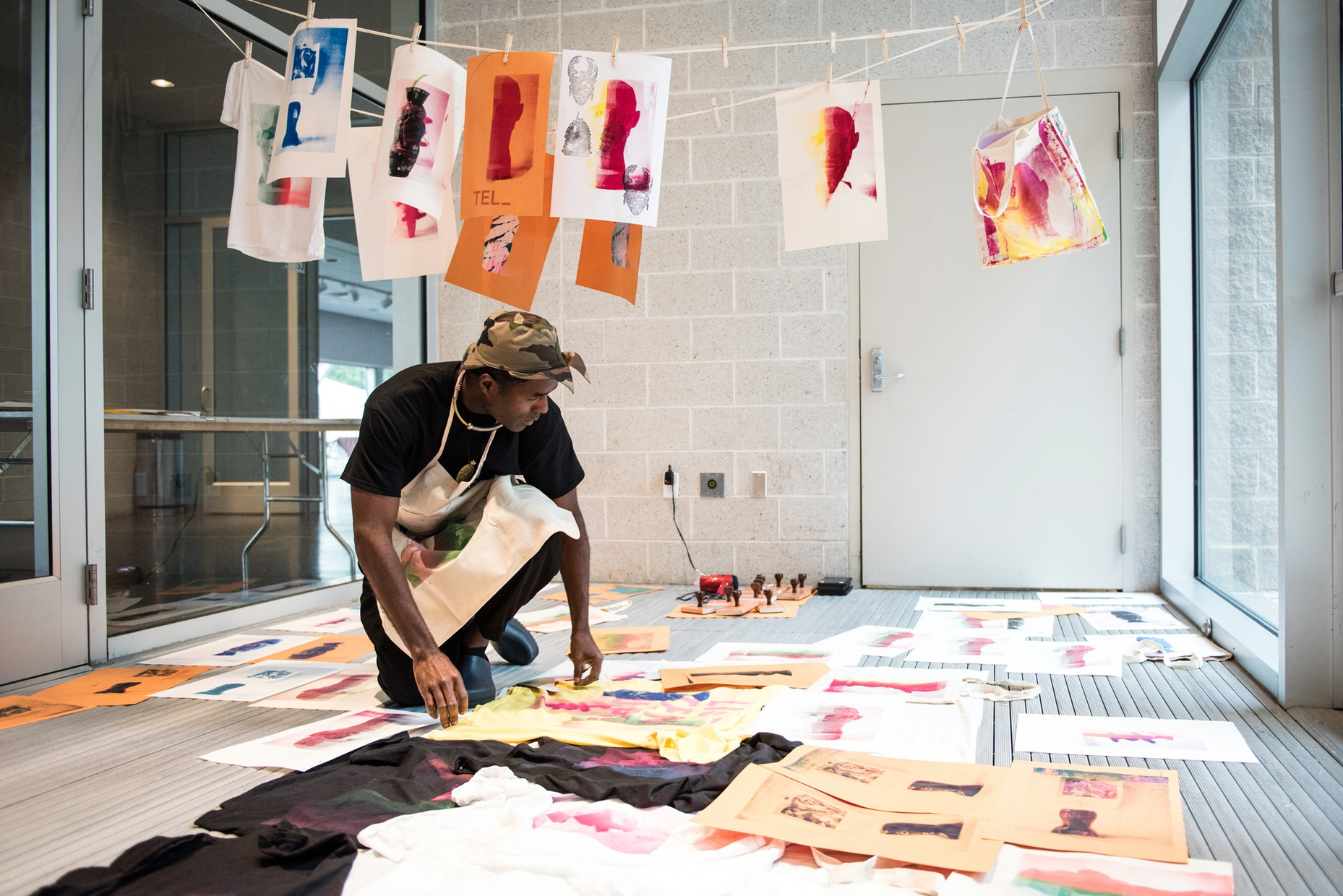 A Black man in an apron crouches in a space filled with prints on paper and t-shirts laid out to dry.