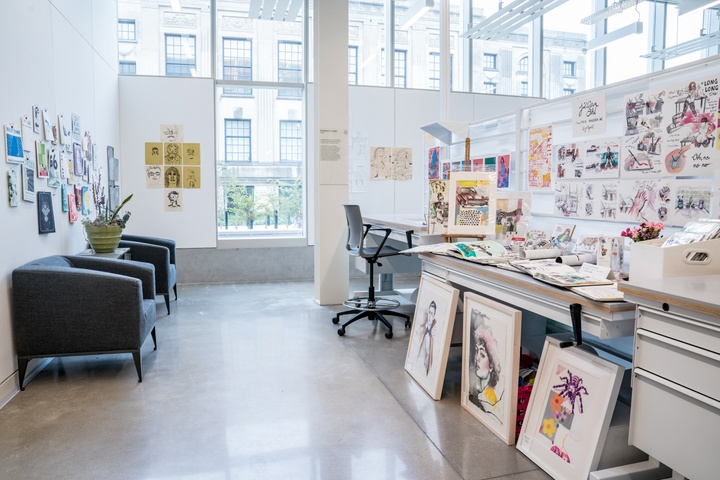 Shared studio space with desks piled with prints and paintings propped up for display. A couple armchairs are tucked in the corner. The back wall is floor to ceiling windows.