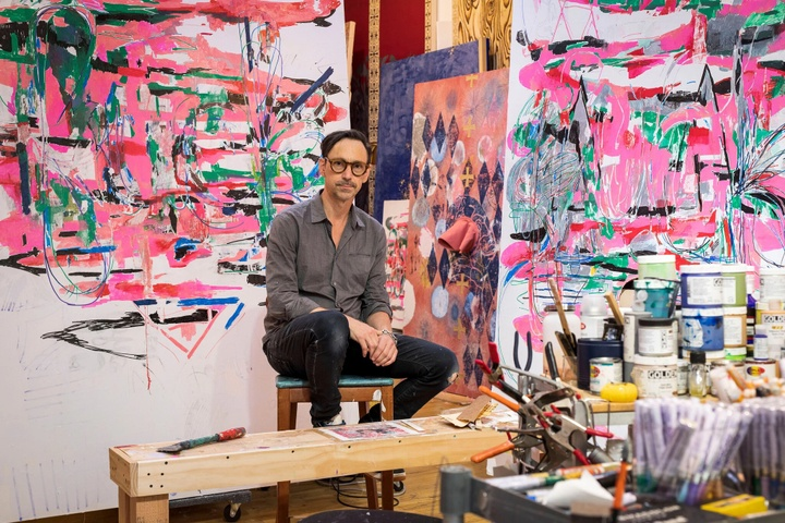 Portrait of Mark Fox in studio, with vibrant paintings on the walls behind him.