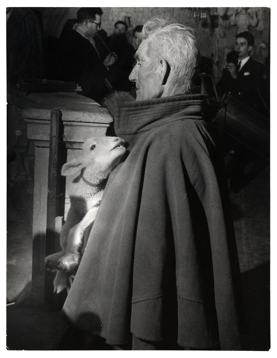 A black and white photograph of an old, light-skinned, stern looking man in a short cloak carrying a lamb.